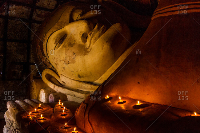 Bagan, Myanmar - December 3, 2012: Large reclining Buddha with lit candles in a temple in Old Bagan