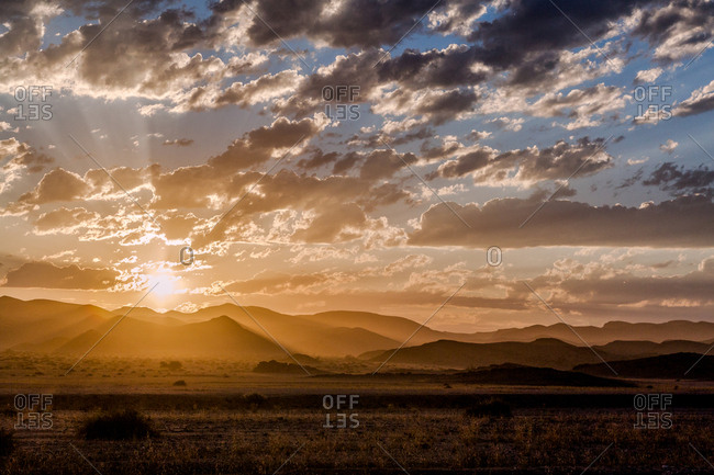 Sun rising over distant mountains and desert at the Hoanib Skeleton Coast, Namibia
