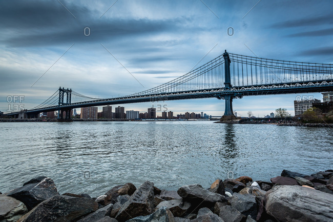 Manhattan Bridge and skyline across the water at twilight