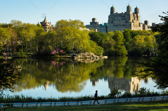New York City, New York - May 7, 2015: Buildings rising over treetops at Central Park Lake