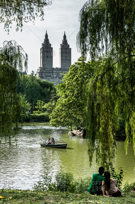 New York City, New York - August, 16, 2014: Couple sitting on a hill overlooking Central Park Lake