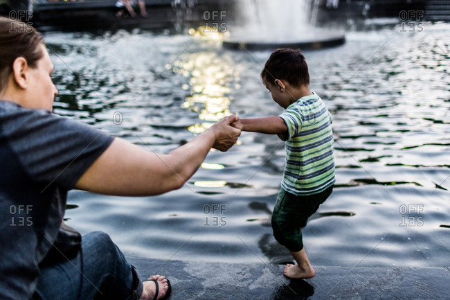 New York City, New York - August 29, 2015: Mother holding her son's hand as he plays in a fountain at Washington Square Park