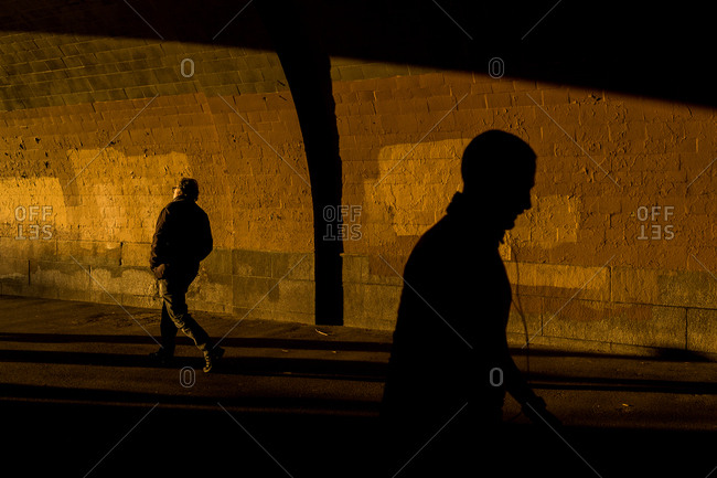 Silhouettes of two men walking through a pedestrian tunnel in Riverside Park, New York City
