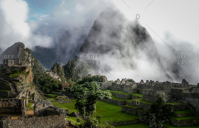 Huayna Picchu mountain shrouded in mist at sunrise at Machu Picchu