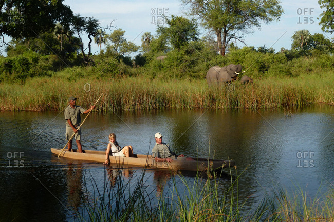 Okavango Delta, Botswana - March 7, 2012: People being guided across a river