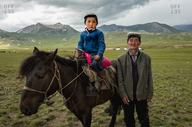 Altai Mountains, Mongolia - July 11, 2016: Kazakh boy on horse by man, Altai Mountains, Mongolia