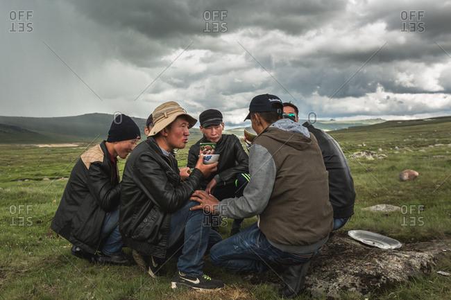 Altai Mountains, Mongolia - July 11, 2016: Kazakh men drinking in a circle, Altai Mountains, Mongolia