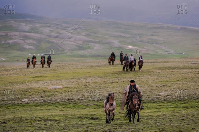 Altai Mountains, Mongolia - July 11, 2016: Kazakh men riding horses, Altai Mountains, Mongolia