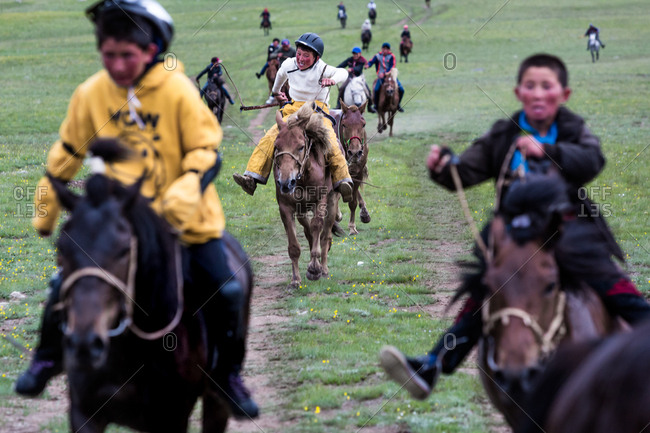 Altai Mountains, Mongolia - July 11, 2016: Kids racing horses together