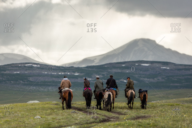Altai Mountains, Mongolia - July 12, 2016: Four men, one boy riding horseback