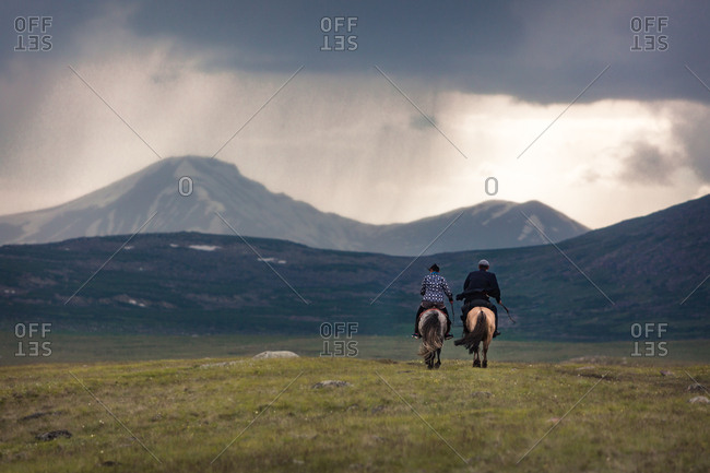 Man and woman riding horses, Altai Mountains, Mongolia