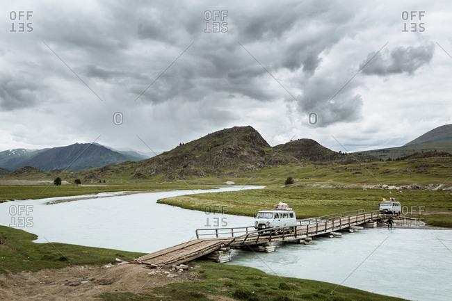 Altai Mountains, Mongolia - July 13, 2016: Vans crossing makeshift river bridge