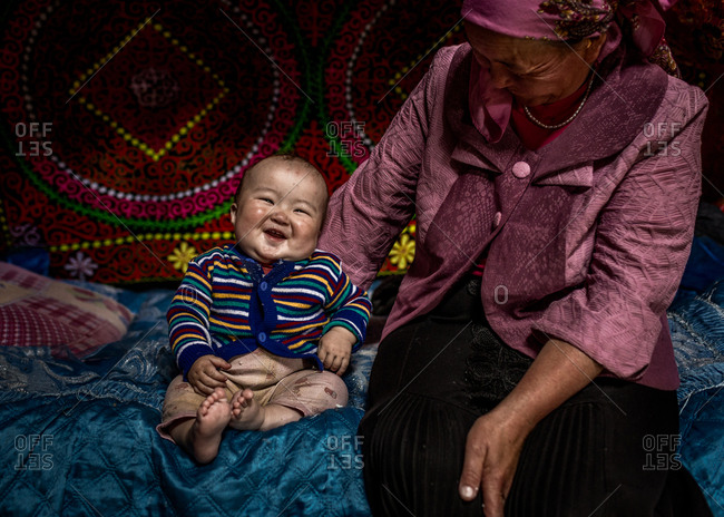 Altai Mountains, Mongolia - July 14, 2016: Happy baby with grandmother