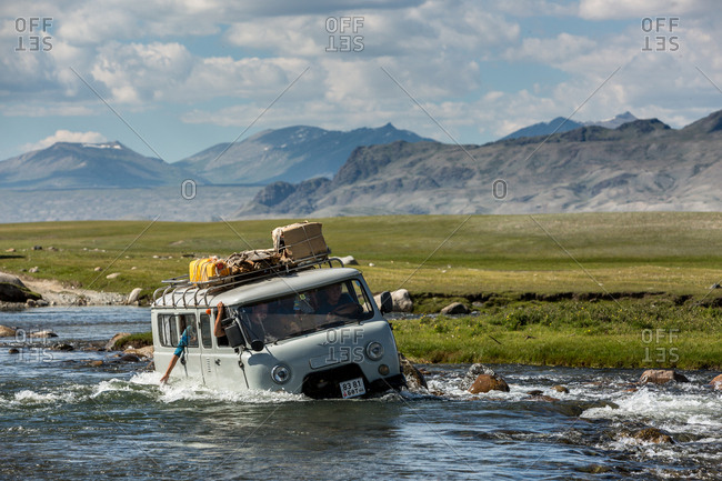 Altai Mountains, Mongolia - July 15, 2016: Van driving in river