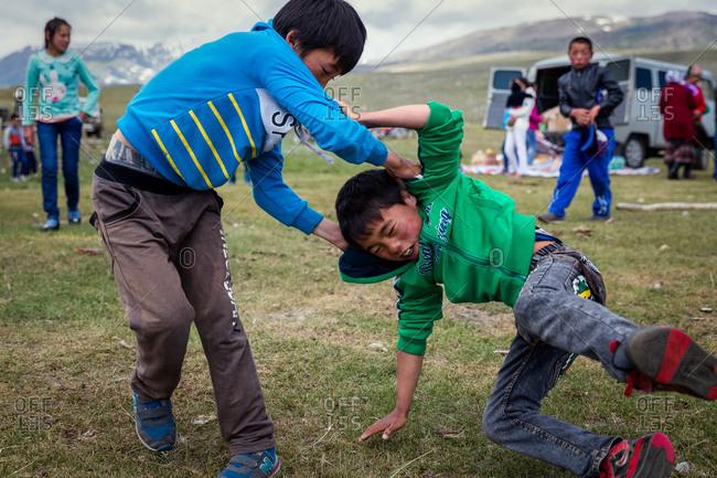 Altai Mountains, Mongolia - July 18, 2016: Kazakh boys wrestling outside