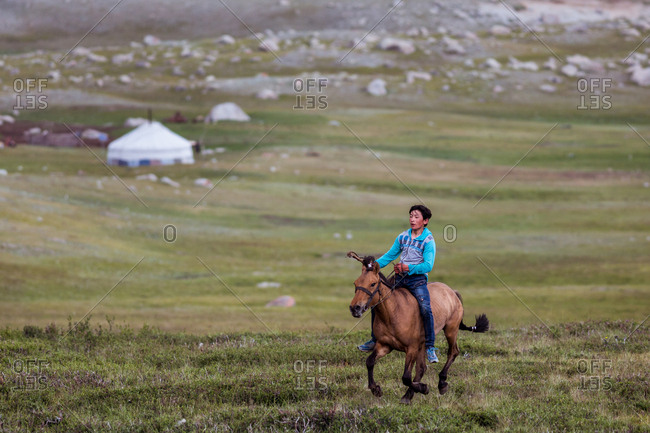 Altai Mountains, Mongolia - July 18, 2016: Young Kazakh boy racing on a horse