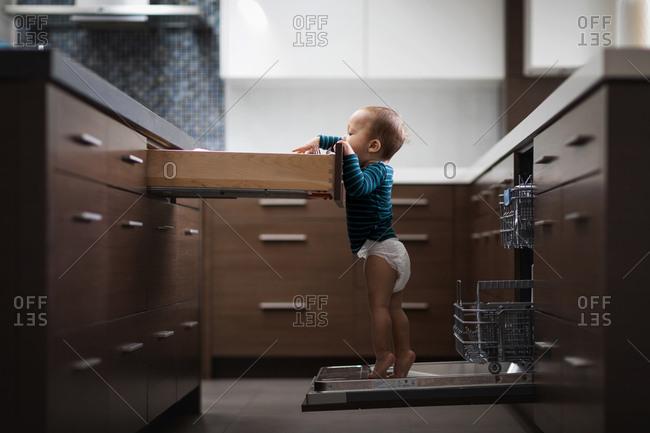Baby boy standing on dishwasher reaching into silverware drawer