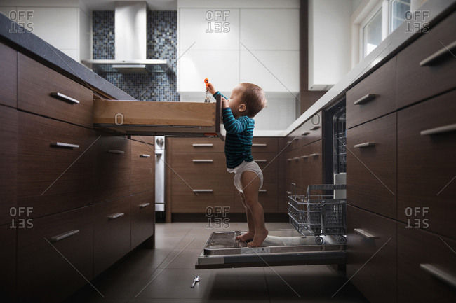 Baby standing on dishwasher reaching into silverware drawer