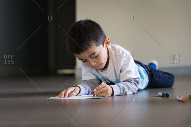 Little boy drawing picture with markers