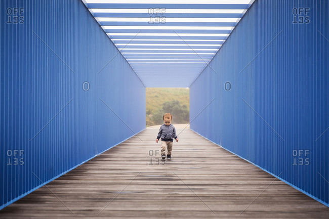 Toddler boy walking on boardwalk