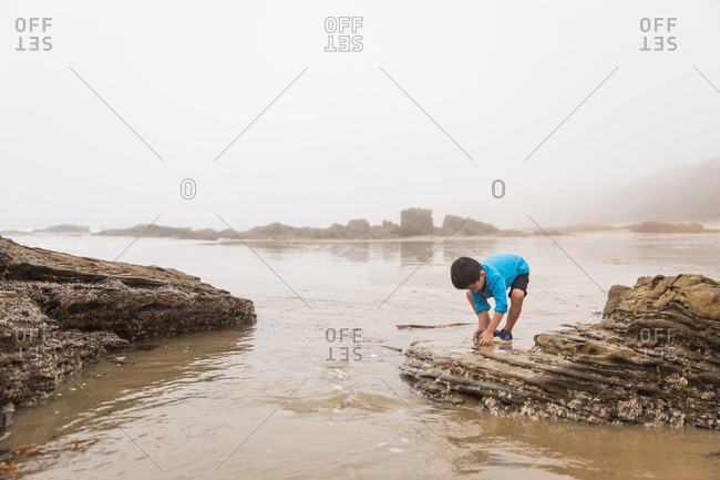 Little boy playing on a rocky beach