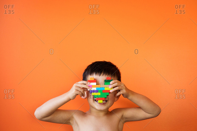 Boy holding heart made from toy bricks in front of his face