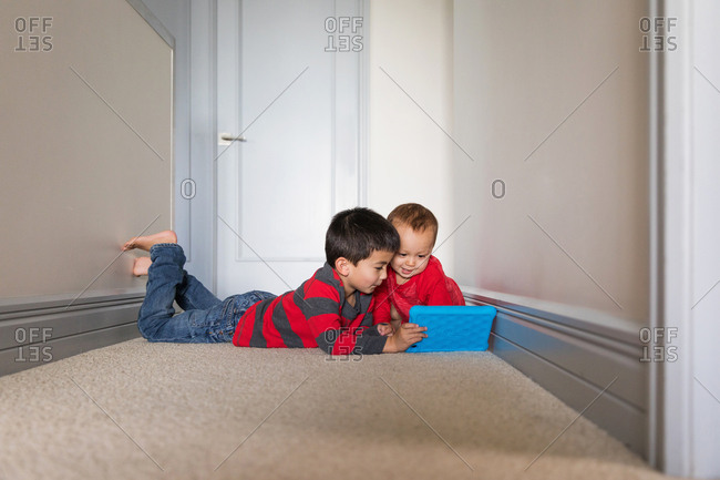 Two little boys playing with a tablet