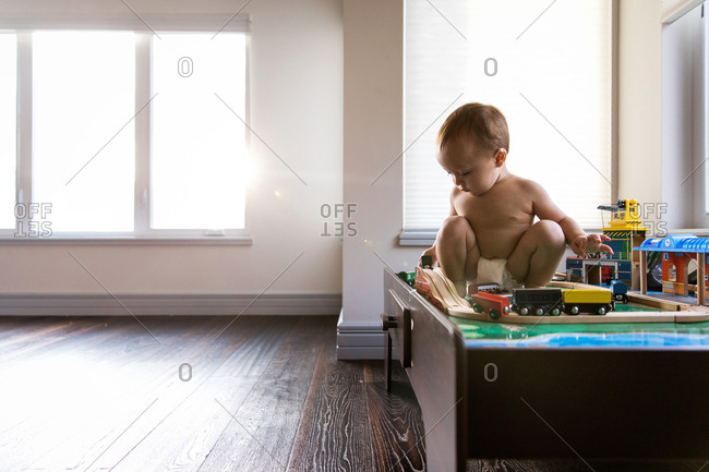 Baby sitting on toy train table