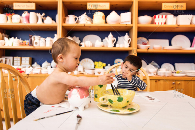 Two boys painting ceramics