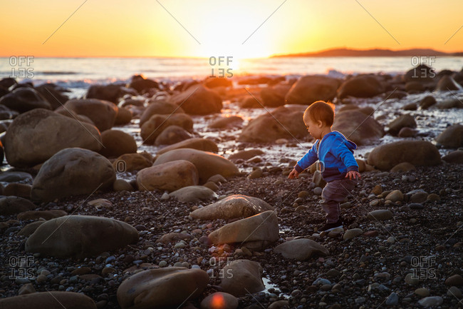 Baby boy playing on a rocky beach at sunset