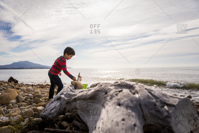 Young boy playing on a rocky beach