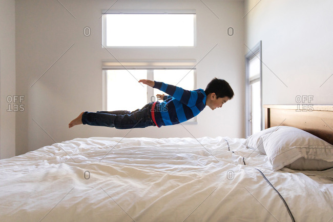 Boy leaping onto bed