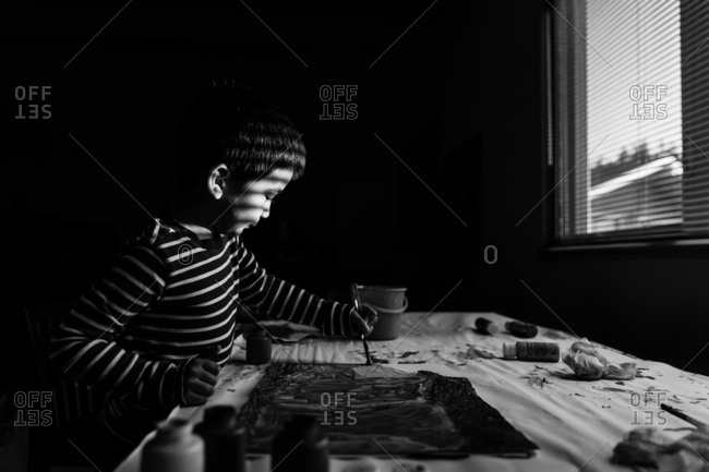Young boy painting a picture in black and white