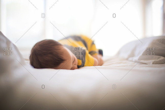 Baby taking nap on a bed