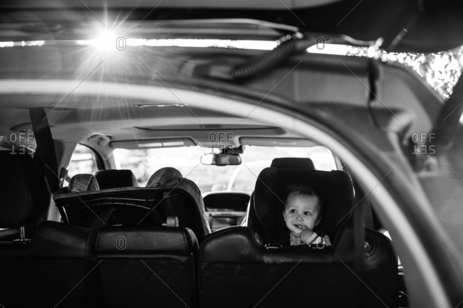 Baby riding in car seat in black and white
