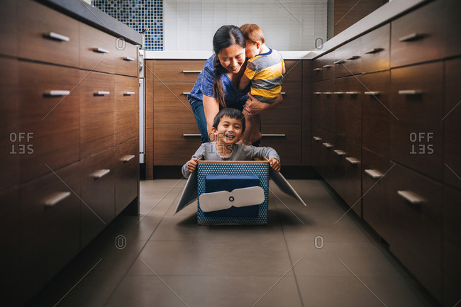 Mother playing with her two sons in a box in the kitchen