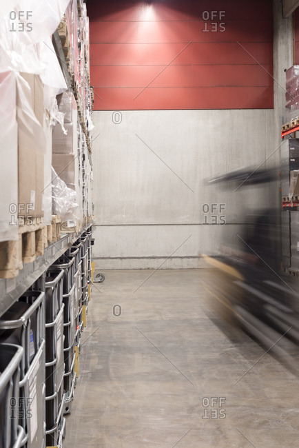 Blurred motion of forklift moving in a factory