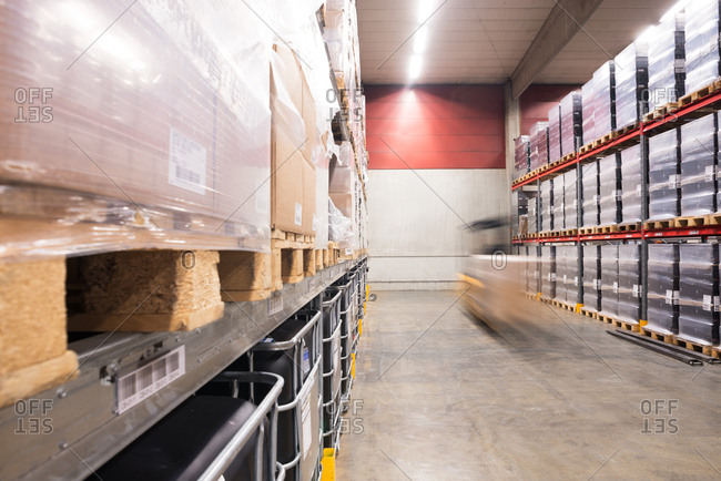 October 25, 2016: Blurred motion of forklift moving pallets in a factory