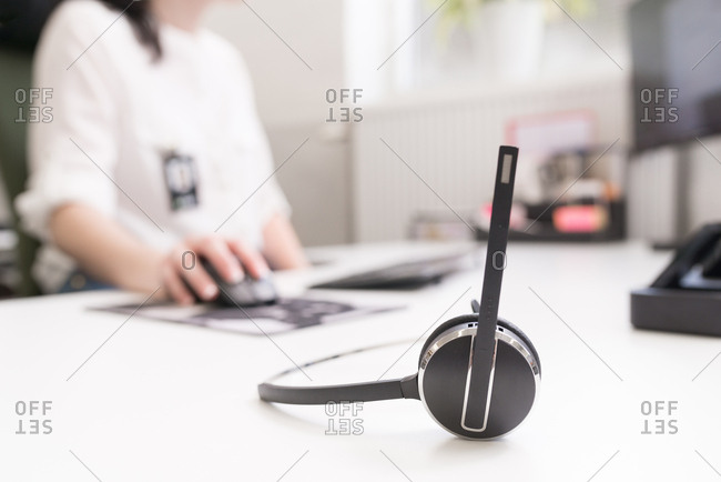 Headset on desk with woman using a computer in background