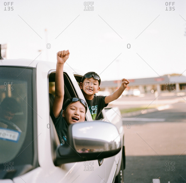 Two excited boys looking out window of a truck