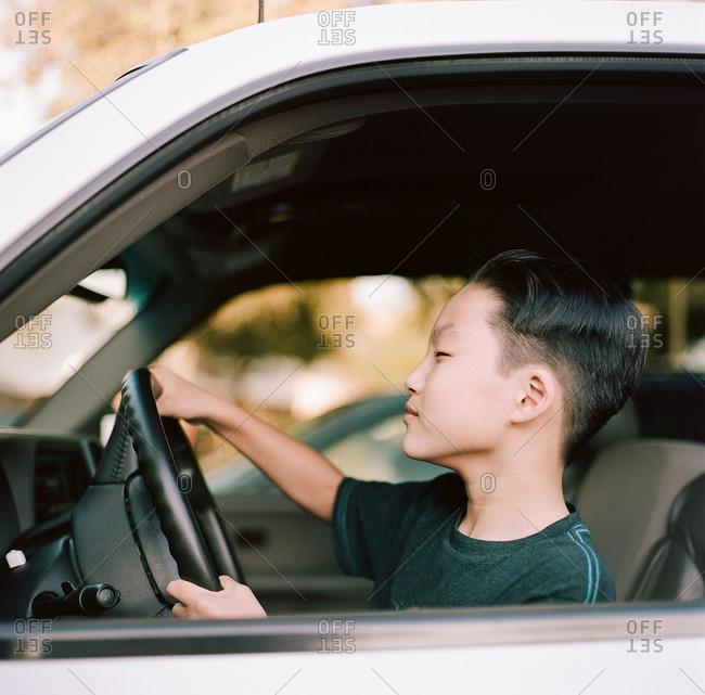 Pre-teen boy pretending to drive a truck
