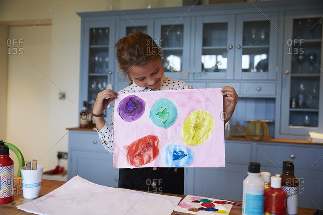 Girl at kitchen table holding picture she has painted