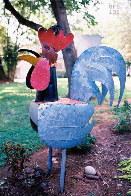 Folk art sculpture of a rooster in a garden