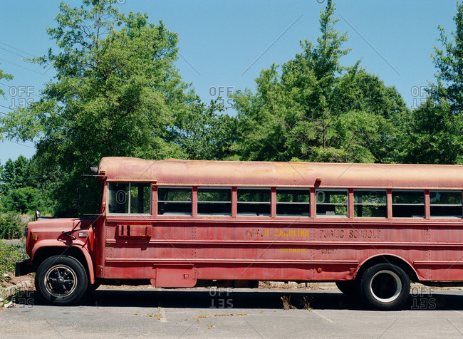 Columbus, North Carolina - June 23, 2016: An abandoned red school bus from the public school system sits quietly in an empty parking lot