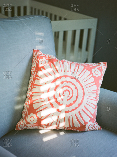Patterned light from window blinds across a decorative pillow on a couch