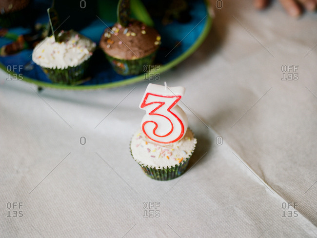 Birthday cupcake with a large candle of the number three
