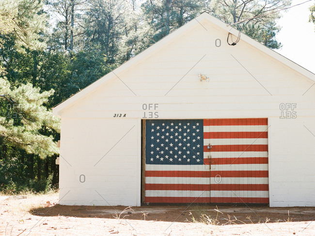 American flag painted on the door to a big white barn