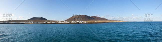 Canary Islands (Spain), La Graciosa . Caleta del Sebo village and la Aguja Grande Volcano, view from the sea
