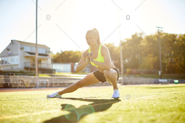 A Young Female Athlete Doing Stretching On The Grassy Field