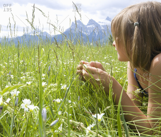 Tween girl lies in alpine meadow